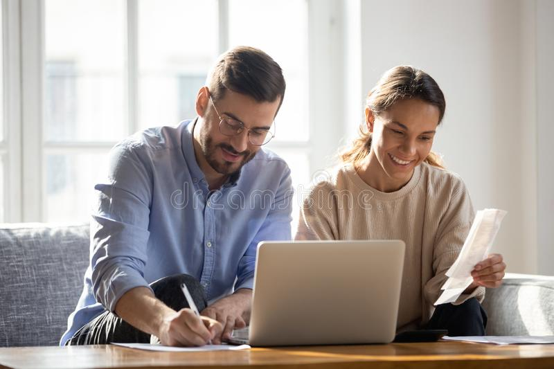 Happy couple using laptop, calculating domestic bills, mortgage documents. Happy couple using laptop, calculating domestic bills, mortgage or loan documents royalty free stock photography