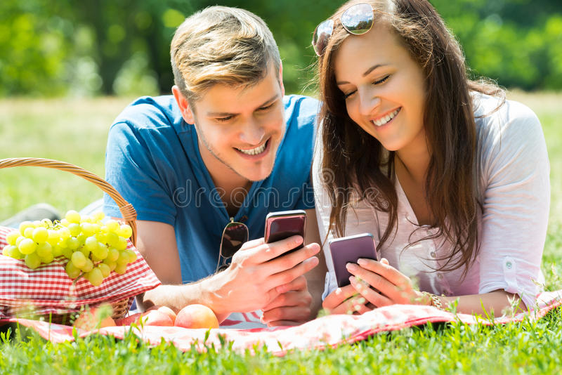 Happy Couple Using Mobile Phone. While Lying In Park royalty free stock images