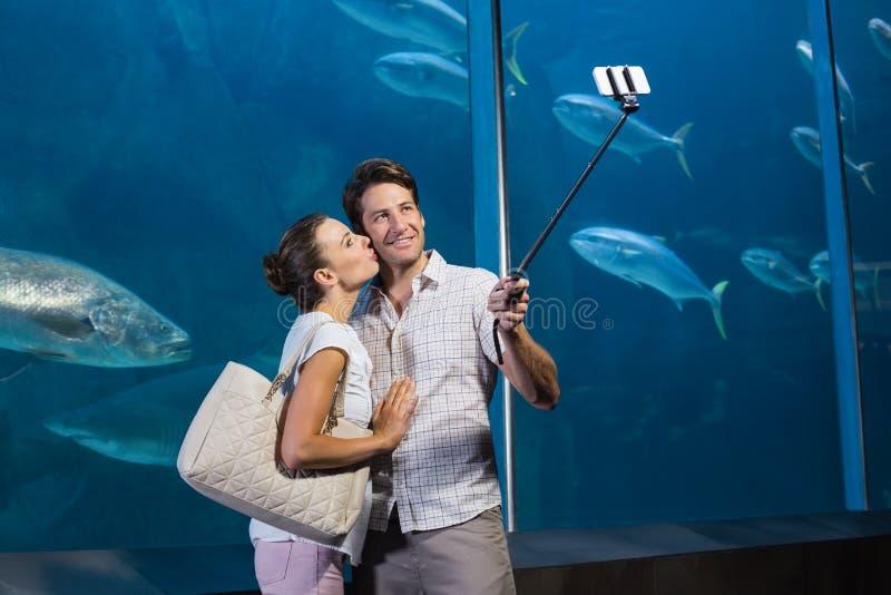 Happy couple using selfie stick. At the aquarium stock photography