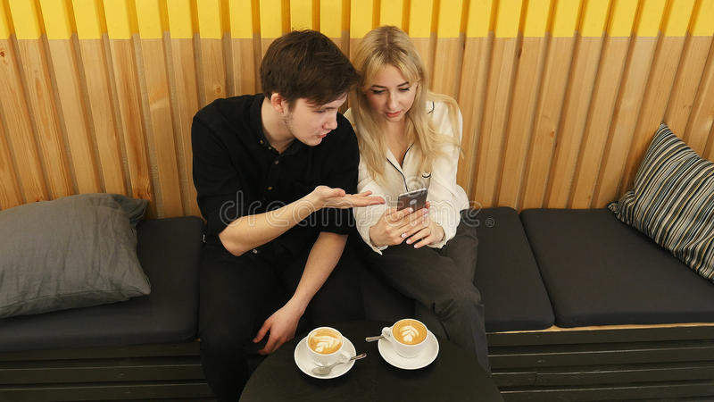 Happy couple using smartphone together and drinking coffee in cafe stock photos