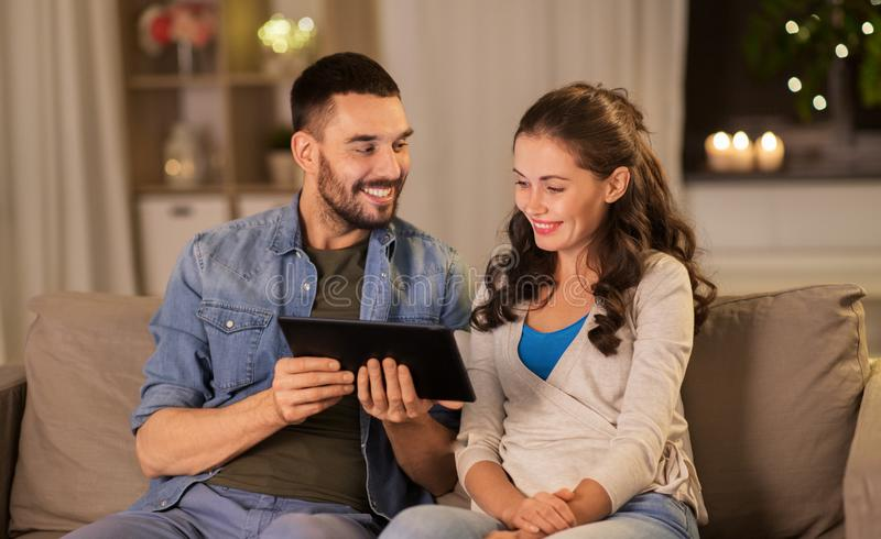 Happy couple using tablet pc at home in evening stock photos