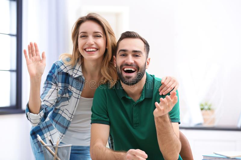 Happy couple using video chat for conversation. Indoors stock photography
