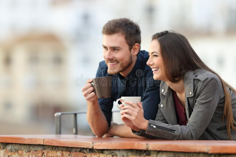 Happy couple on vacation drinking looking away stock image
