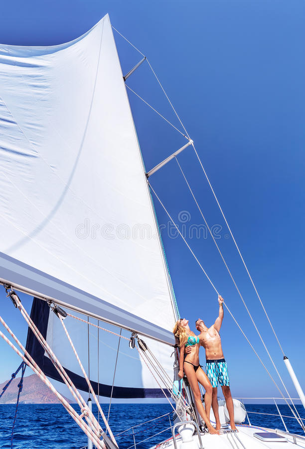 Happy couple in vacation. Happy couple in honeymoon vacation in luxury sea cruise, enjoying each other and travel on beautiful sailboat, looking up in the sky royalty free stock photos