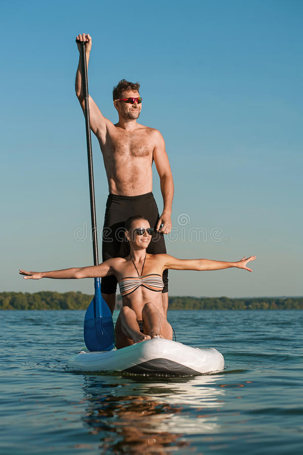 Happy couple on vacation sport kayak SUP newlyweds stock photo
