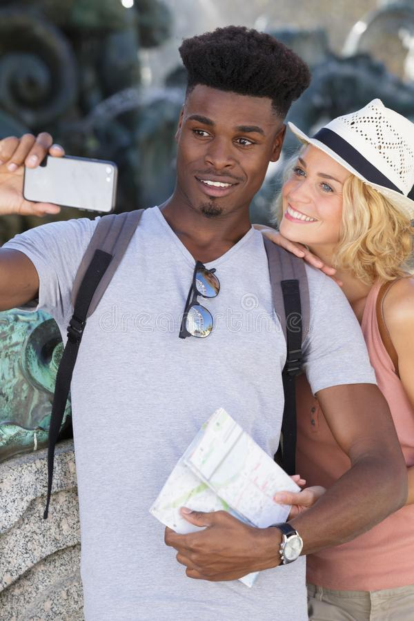 Happy couple on vacation taking selfie on city street royalty free stock image