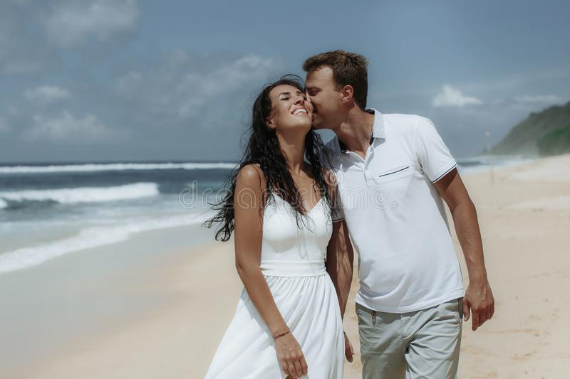 Happy couple walking at the beach, traveling at Bali. royalty free stock photography