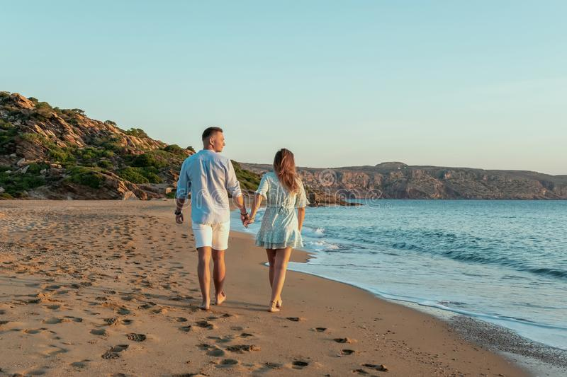 Happy couple is walking on the beach during sunset or sunrise. Summer vacations.  royalty free stock image