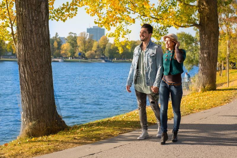 Happy couple walking in a park by the water in autumn royalty free stock image