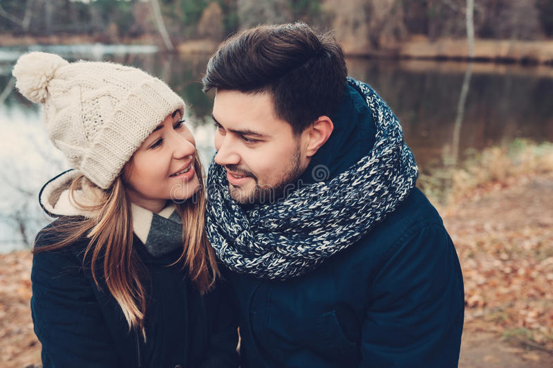 Happy couple in warm knitted hat and scarf walking outdoor in autumn forest. Cozy mood royalty free stock image
