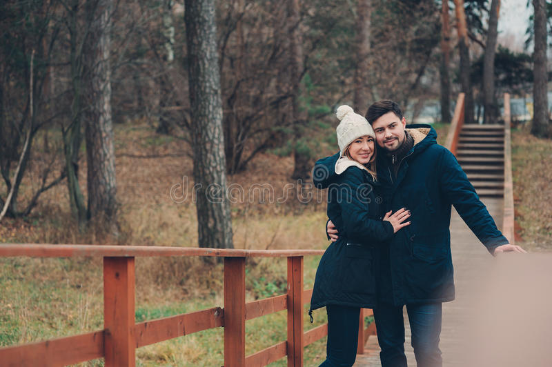 Happy couple in warm knitted hat and scarf walking outdoor in autumn forest. Cozy mood royalty free stock images