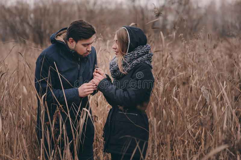 Happy couple in warm knitted hat and scarf walking outdoor in autumn forest. Cozy mood stock photo
