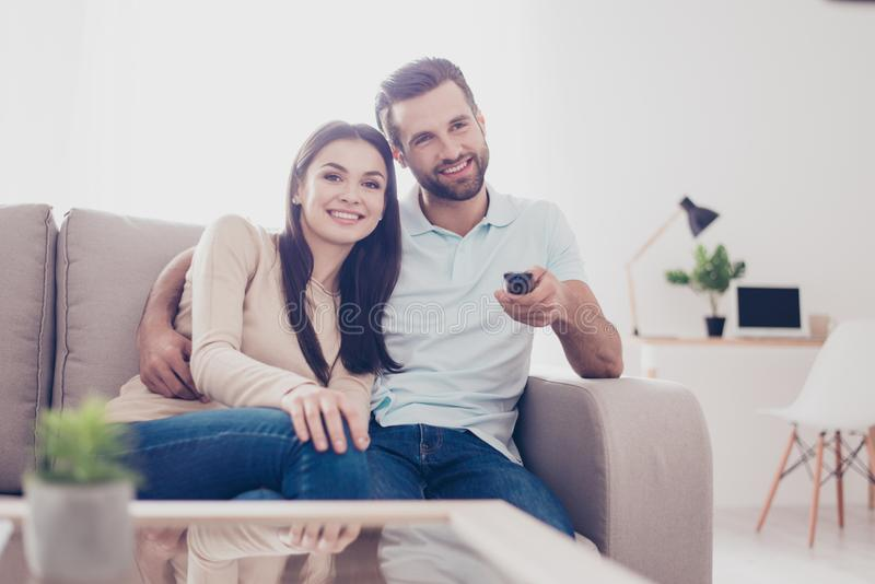 Happy couple is watching movie at home, hugging. They sit on sofa in nice livingroom stock images