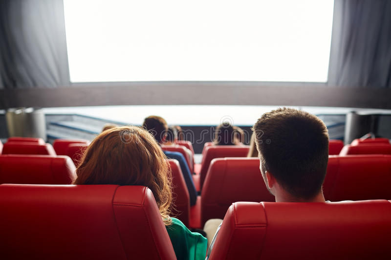 Happy couple watching movie in theater or cinema royalty free stock image