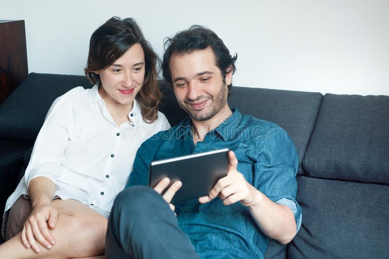 Happy couple watching movies on digital tablet royalty free stock images