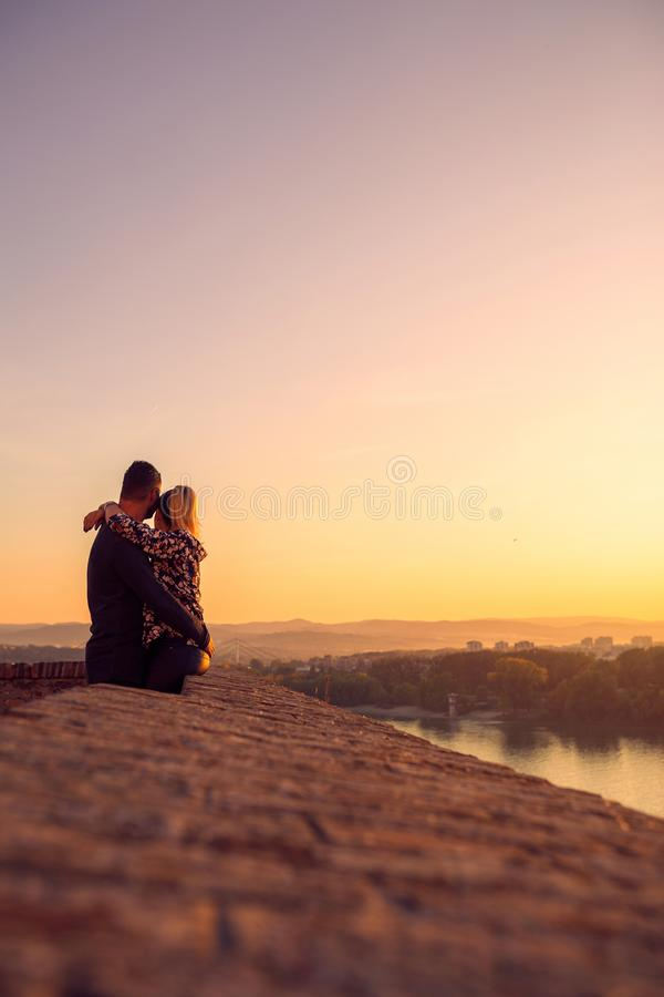 Happy couple watching the sunset stock photography