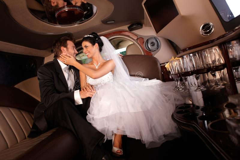 Happy couple on wedding-day. Happy couple embracing in limousine on wedding-day stock photos