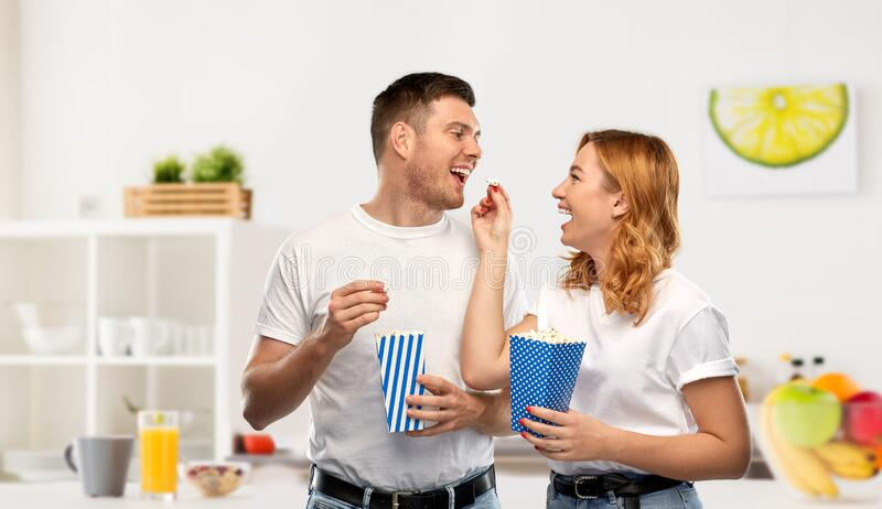 Happy couple in white t-shirts eating popcorn stock photo