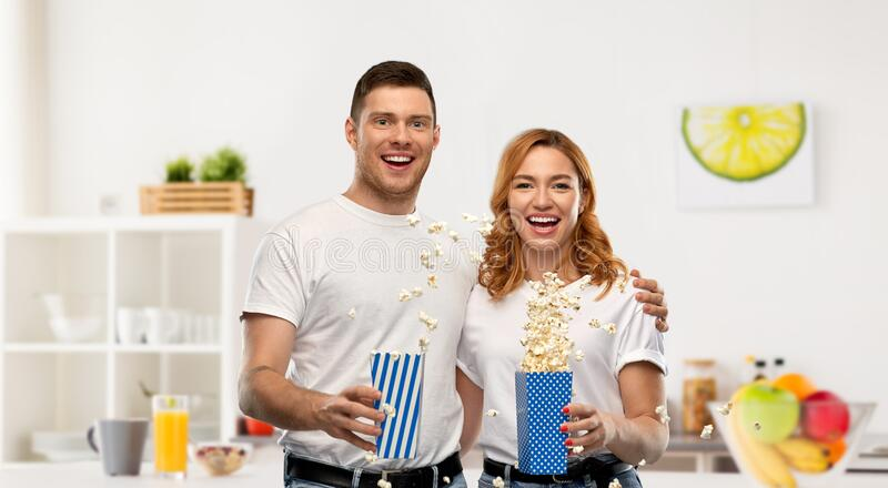 Happy couple in white t-shirts eating popcorn royalty free stock photography