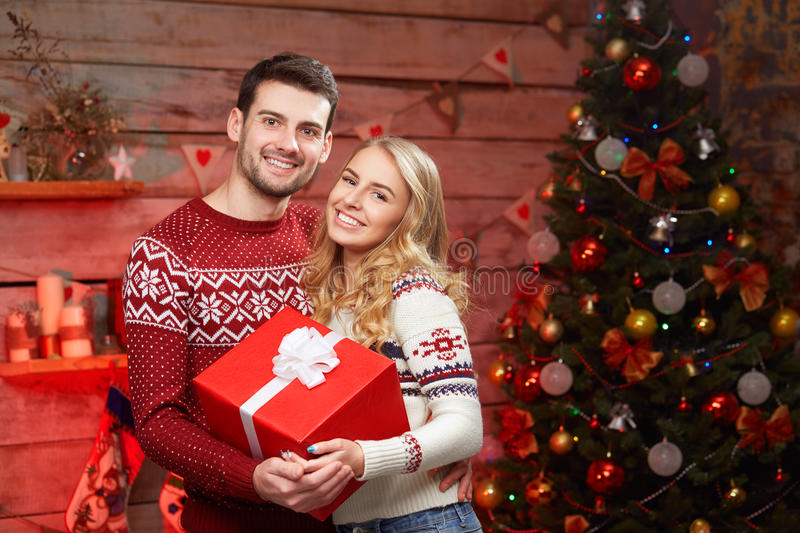 Happy Couple in winter pullovers smiling and holding big red gift box royalty free stock images