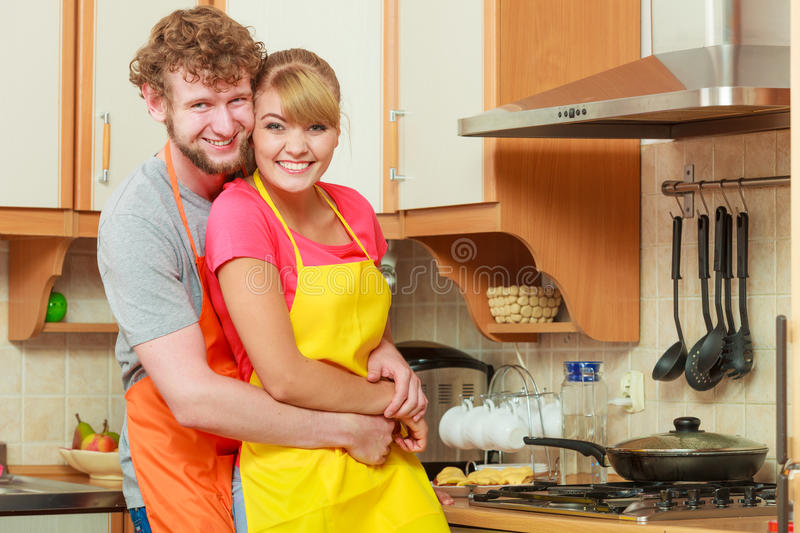 Happy couple woman and man frying chicken cutlet. stock photography