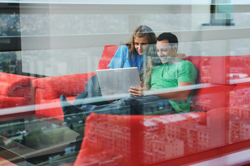 Happy couple work on laptop at home royalty free stock photos