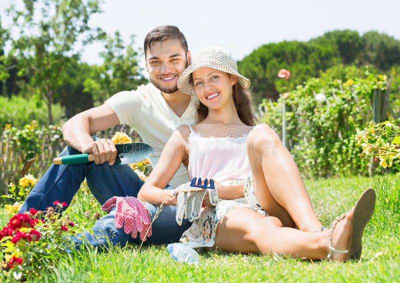 Happy couple working in garden. Happy laughing couple working in the flower garden royalty free stock image