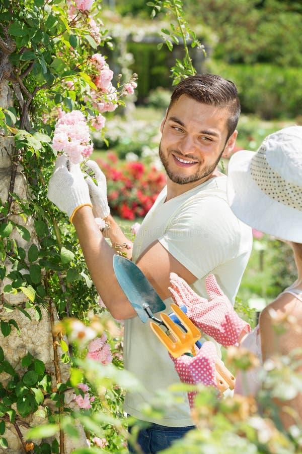 Happy couple working in garden. Happy smiling couple working in the flower garden stock photography