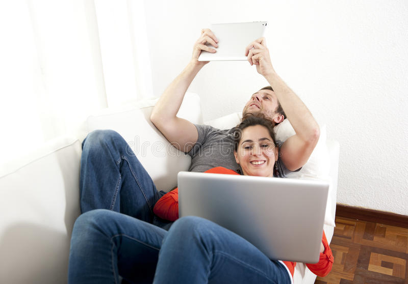 Happy couple working on their laptop and tablet on a sofa. Happy couple sitting on a sofa, couch working on their laptop and tablets in a white living room stock images