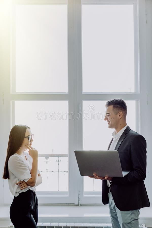 Happy couple of young business partners working in modern office. Two coworkers working on laptop while standing near window, copy royalty free stock photo