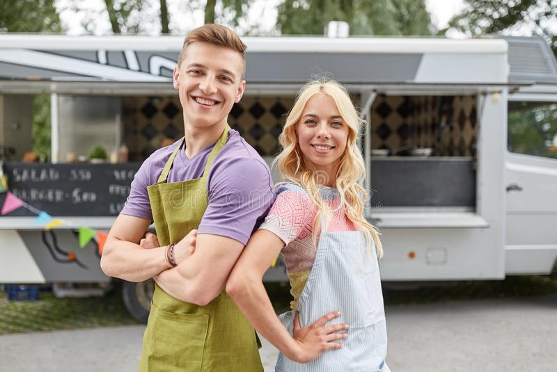 Happy couple of young sellers at food truck. Street sale and people concept - happy couple of young sellers at food truck stock photo