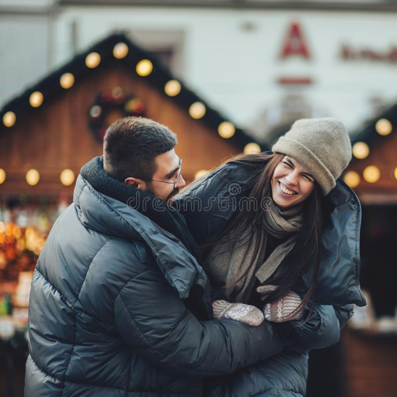 Happy couples on the city square decorated for a Christmas marke royalty free stock images