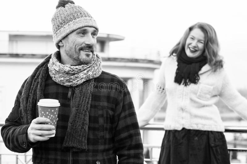 Happy couples loves drink coffee outdoor. Smiling guy holds craft cup with coffee and hiding it from girlfriend behind. royalty free stock images