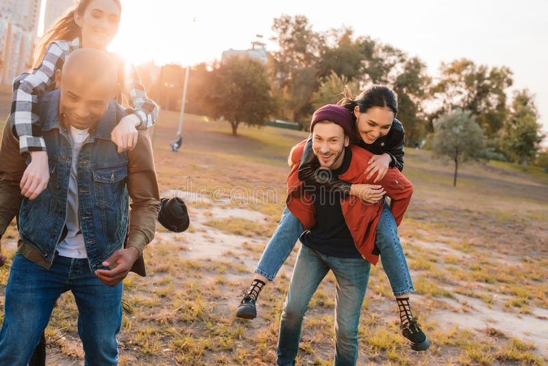 Happy couples piggybacking together. Happy multiethnic couples piggybacking together in park royalty free stock photography