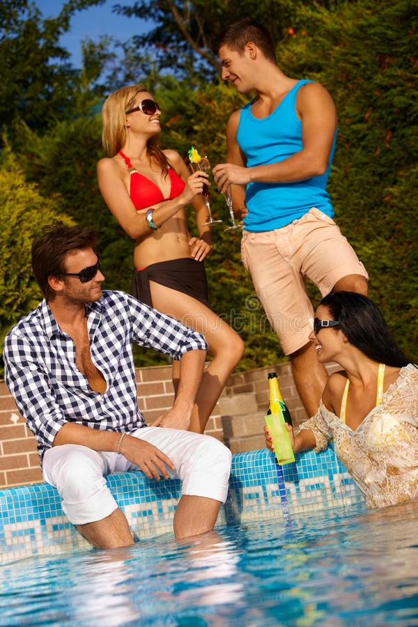 Happy couples at summer. Happy young couples having fun by swimming pool stock photography