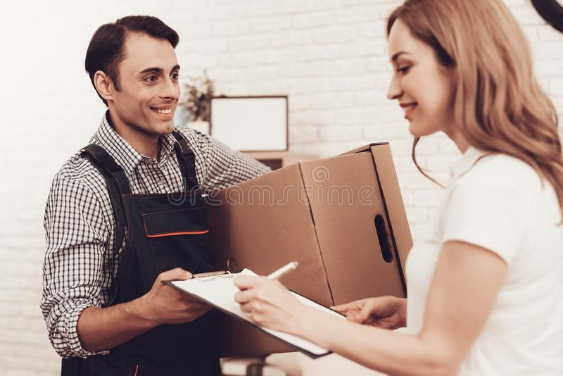 Happy Courier in Blue Clothes and Girl Sign Paper. Courier Delivery. Man with Brown Box. White Interior. Deliveryman Arab Nationality. Courier in Blue Clothes royalty free stock photo