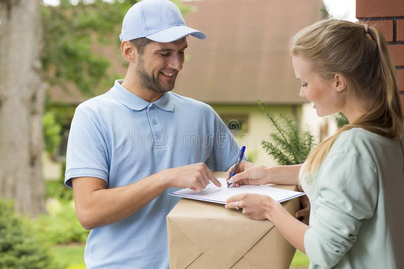 Courier in blue uniform and woman signing receipt of package delivery. Happy courier in blue uniform and women signing receipt of package delivery royalty free stock photos