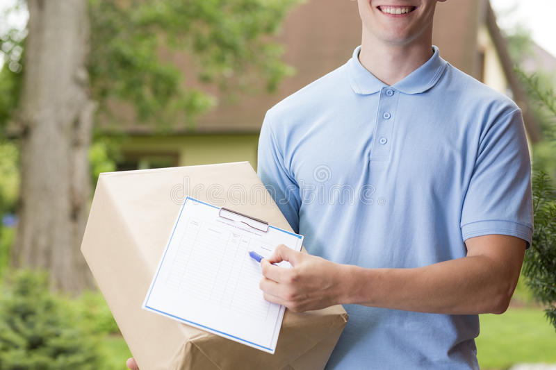 Happy courier holding a package stock photos