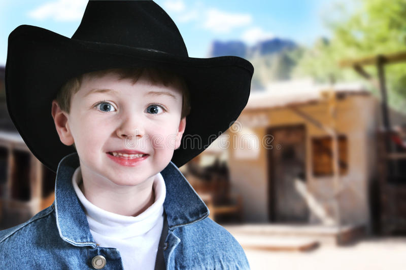 Happy Cowboy in Old West. Happy four year old boy in cowboy hat and denim jacket in the old west stock photo