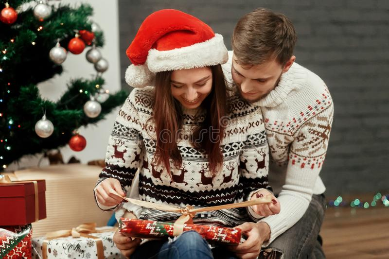 Happy cozy family moments in winter holidays. stylish excited co. Uple opening presents at decorated christmas tree. seasonal greetings concept. space for text royalty free stock photos