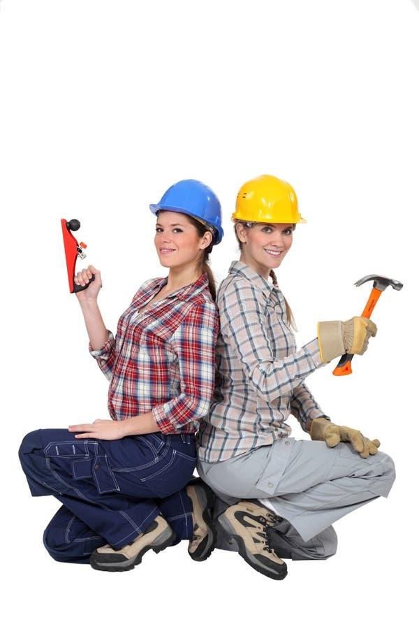 Happy craftswomen back to back stock photos
