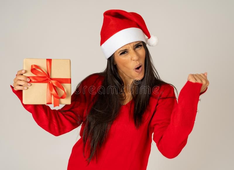 Happy crazy excited young woman in santa claus hat with christmas present laughing and smiling stock photos