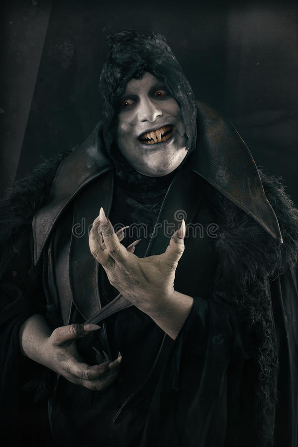 Happy crazy smiling vampire with large scary nails. Undead monster royalty free stock photo