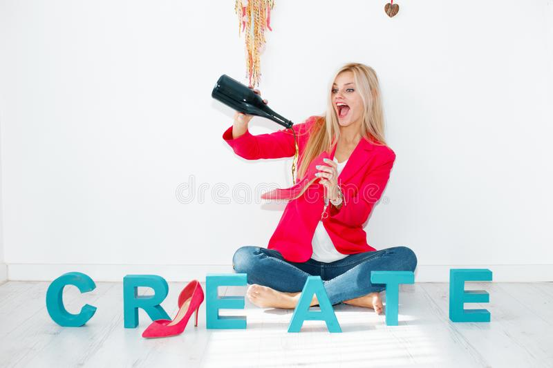 Happy creative woman streaming champagne to high heels royalty free stock image