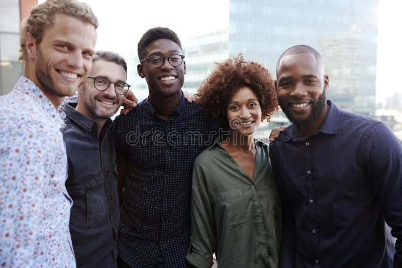 Happy creative business colleagues smiling to camera outdoors, waist up, close up stock photography