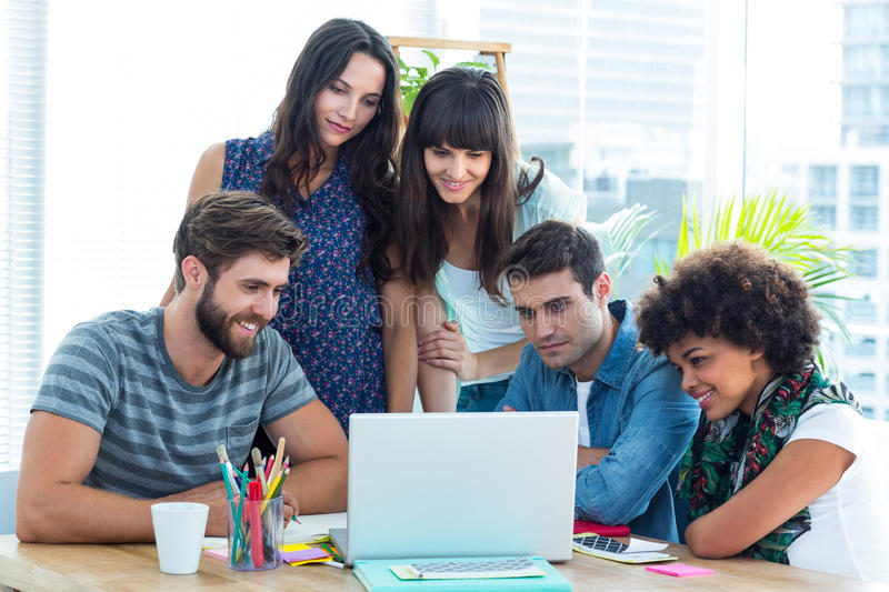 Happy creative business team gathered around a laptop royalty free stock images