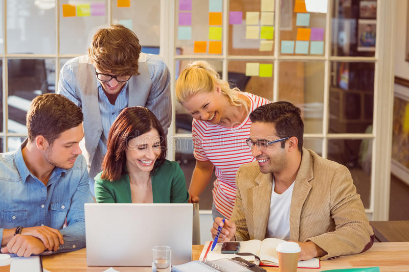 Happy creative business team using laptop in meeting stock images