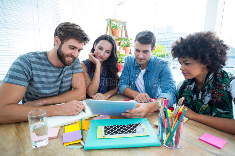 Happy creative business team using tablet in meeting royalty free stock photos