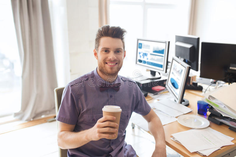 Happy creative male office worker drinking coffee. Business, startup and people concept - happy businessman or creative male office worker with computers royalty free stock photography