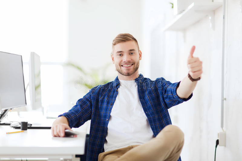 Happy creative man with computer at office. Business, technology, education and people concept - happy young creative man or student with computer at office at royalty free stock photos